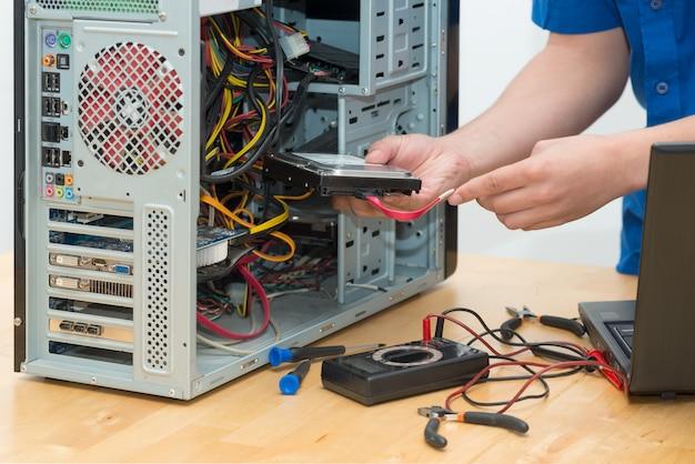 彼のオフィスで壊れたコンピューターに取り組んでいる若い技術者