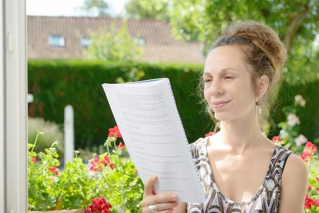 若い女性は窓の近くを読み取ります