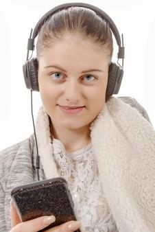 彼の携帯電話で音楽を聴く若い女性