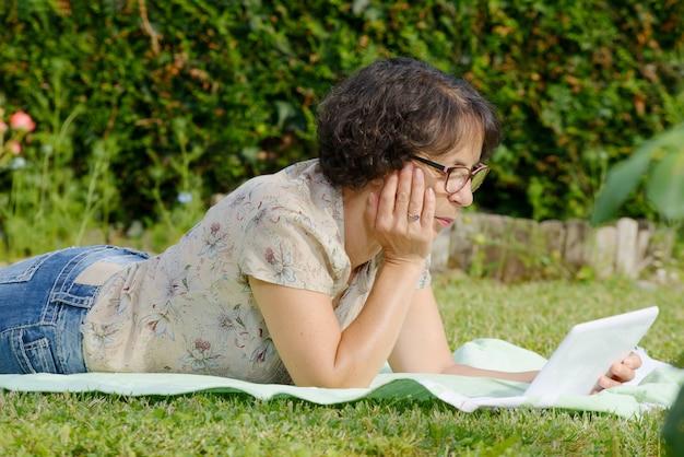 Зрелая женщина отдыхает в саду