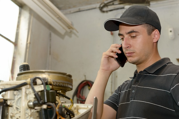 Механик молодого человека ремонтируя моторные лодки и телефон на клиенте