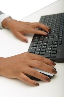 Руки молодой африканской женщины с помощью компьютера