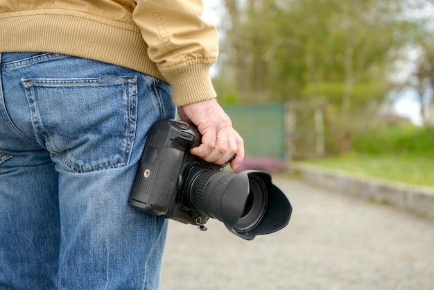 彼の写真カメラを保持している写真家
