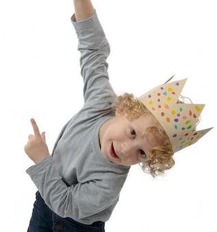 Белокурый маленький мальчик с короной на голове, на белом