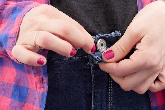 女性は彼女のジーンズをボタン留め