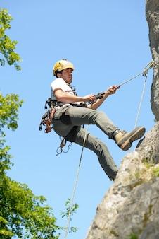 岩の壁を登る若い男