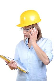 黄色いヘルメットを持つ若い女性建築家