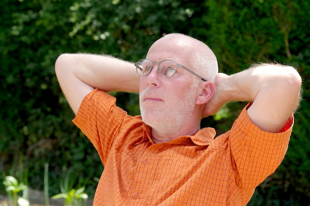 庭でリラックスした成熟した男の肖像