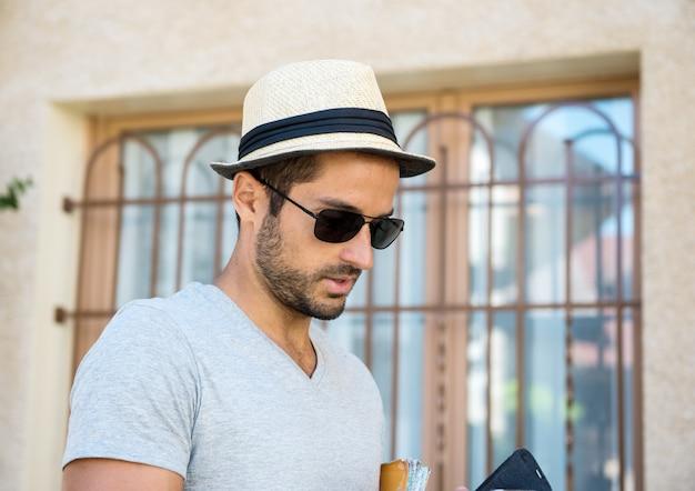 帽子とサングラスを持つ若い男の肖像