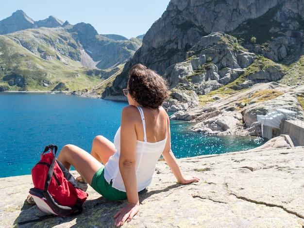 山の湖の近くに女性ハイカーがかかっています。