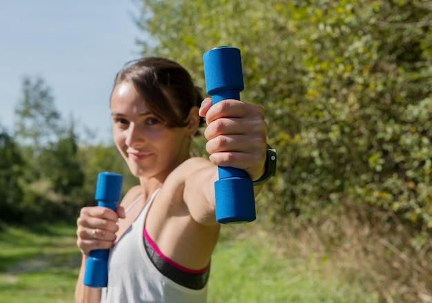 Фитнес женщина делает упражнения с гантелями