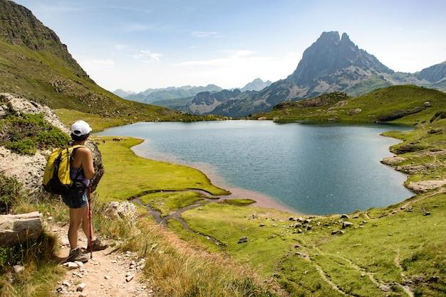 山の湖の近くのハイキングの女性