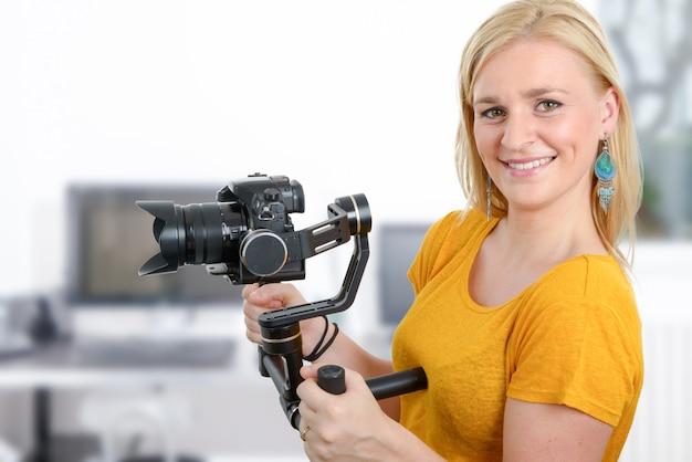 安定したカムを使用して女性のビデオ撮影