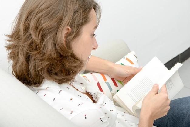 ソファで本と美しい若い女性
