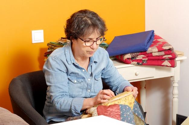 縫製のための女性はキルトを終了します。
