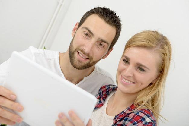 デジタルタブレットを使用して幸せな若いカップル