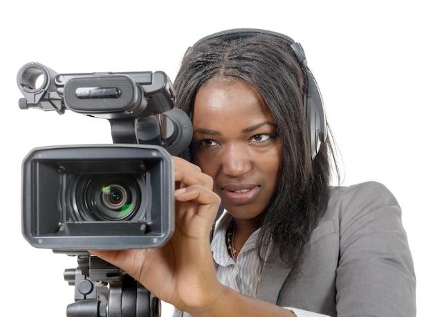 プロのビデオカメラとヘッドフォンを持つ若いアフリカ系アメリカ人女性