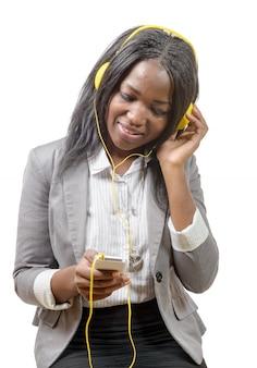 陽気な魅力的なアフリカの女の子の携帯電話を保持していると音楽を聴く