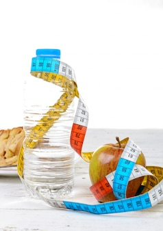 水のボトルとメーターリボン付きリンゴ