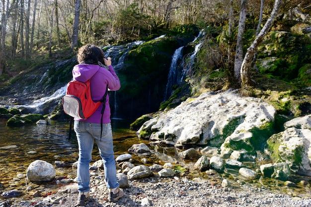 秋の滝を撮影する女性写真家