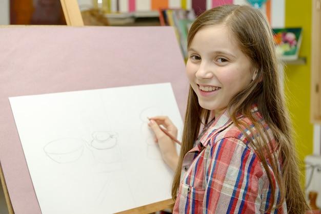 笑顔の若いアーティストの女の子を描く