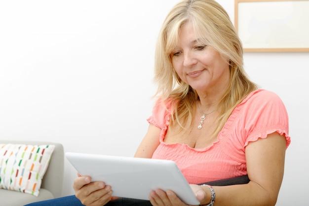 自宅でタブレットを使用して美しい成熟した女性