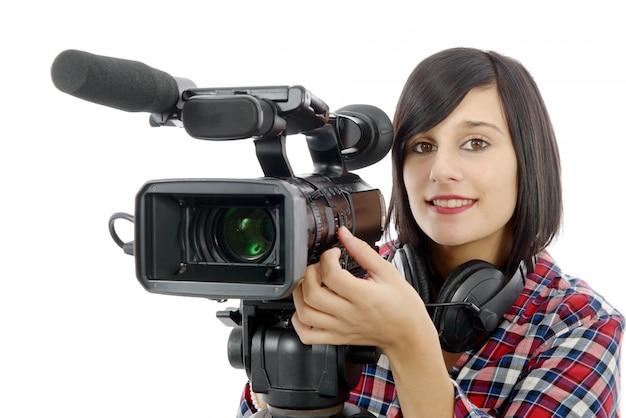 白のプロのビデオカメラでかなり若いブルネットの少女
