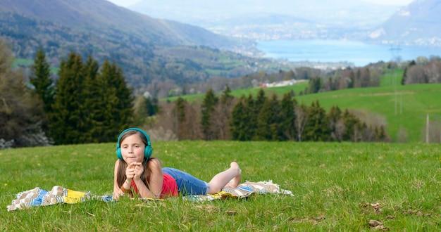 自然の中で音楽を聴くかなり若い女の子