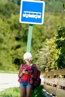 白い帽子、バスを待っている学校の女の子