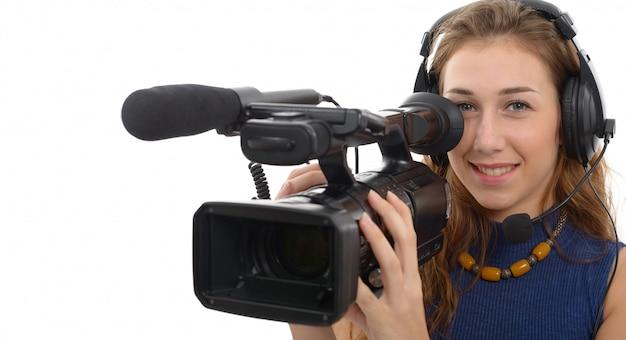 白い背景の上のビデオカメラを持つ若い女性