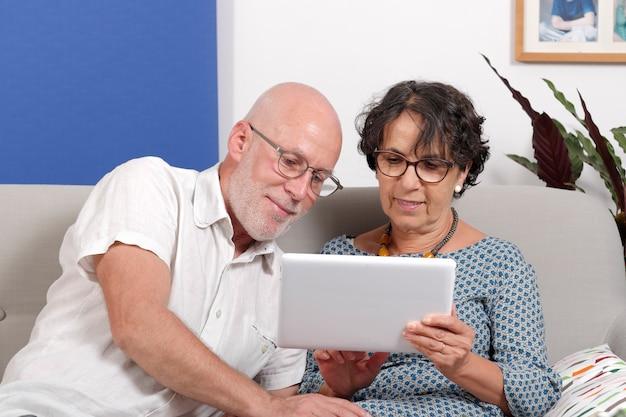 Пожилая пара с помощью планшета и улыбки