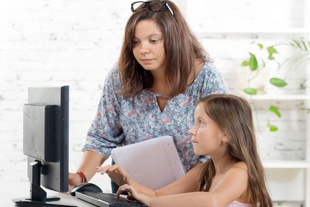 若い先生がコンピューターで女子高生を助けます