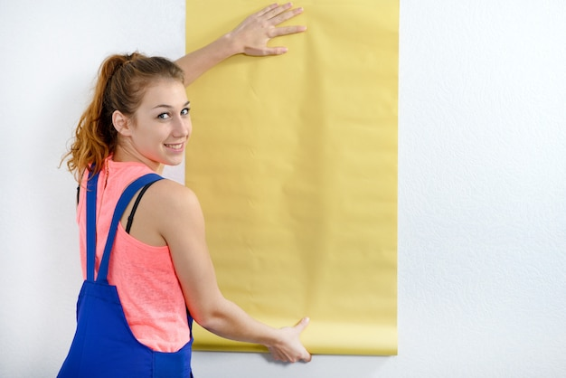 Молодая женщина с рулоном желтых обоев