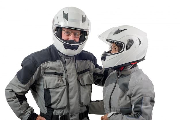 白い背景で隔離のヘルメットとカップルシニアライダー