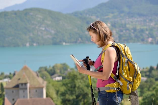 Молодая и красивая женщина ищет свой путь для похода в горы