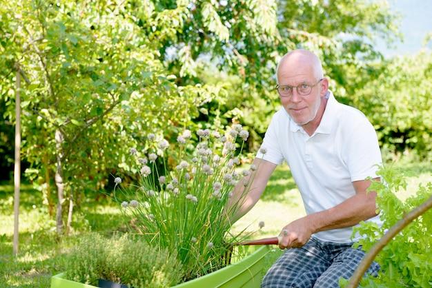 彼の庭でハンサムな年配の男性