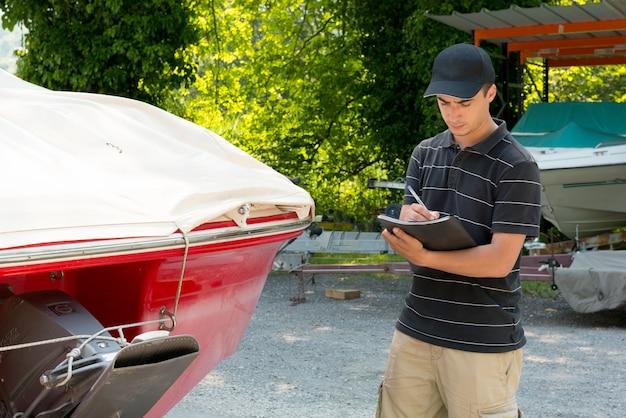 若いメカニックがモーターボートをチェック