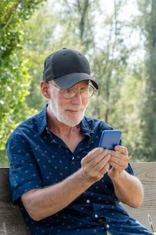 スマートフォンを使用して野球帽の肖像画で年配の男性