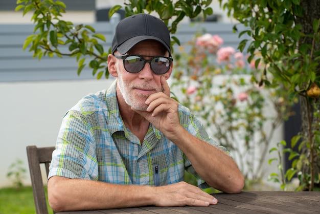 Старший мужчина в бейсболке с солнцезащитные очки, отдыхая в саду