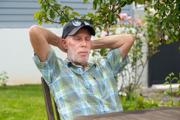 Старший мужчина в бейсболке расслабляющий в саду, портрет