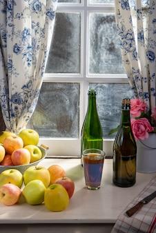 ボトルとリンゴとサイダーのガラス。素朴な家の窓の近く