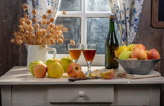 ボトルとテーブルの上のリンゴとサイダーのグラス。素朴な家で