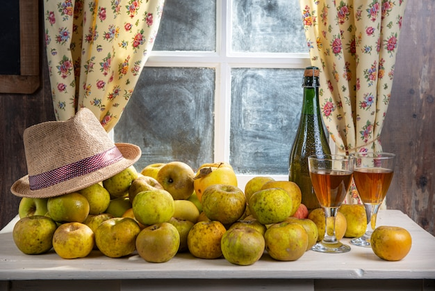 ボトルと素朴な家の窓の近くのリンゴとサイダーのグラス