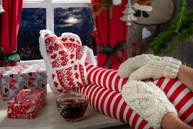Женщина ноги с носками на столе и фоне окна, рождественские концепции
