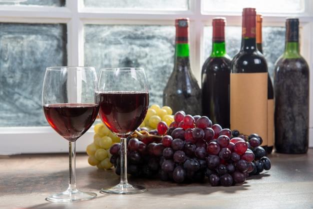 Композиция с двумя рюмками, виноградом и бутылками красного вина
