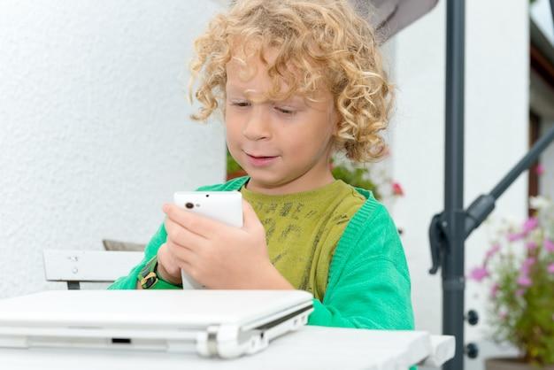 スマートフォンを使用して小さな金髪の少年の肖像画