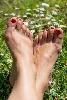 Женщина босиком на весенней траве и цветы ромашки