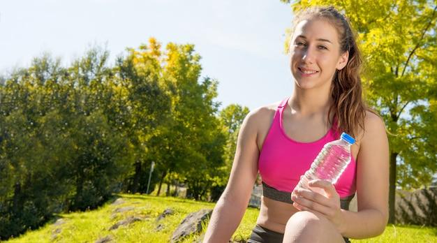 Счастливая девушка питьевой воды в фитнес