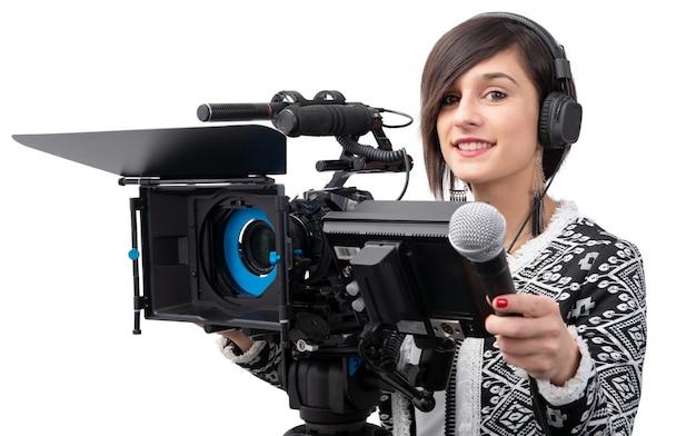 Милая журналистка молодой женщины с микрофоном в студии телевидения на белизне