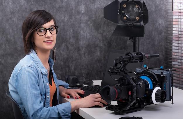 Видео редактор молодой женщины работая в студии